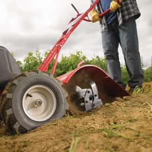 Man plowing a field using a gas powered tiller