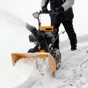 Yellow snow blower pushed by a man during snowfall