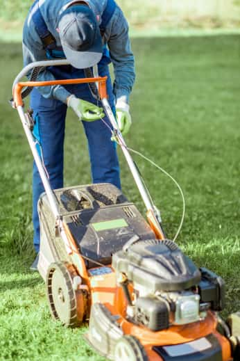 Gardener adjusting a cable on a lawnmower